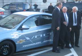 Photo of a small blue car, the Chevy Volt, with GM CEO Rick Wagoner, Senator Carl Levin and Rep. Sander Levin standing alongside the car.
