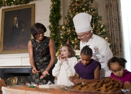 First Lady Michelle Obama and White House Pastry Chef Bill Yosses laugh as young visitor tastes her decorated cookie during a holiday craft demonstration with the children of military personnel in the State Dining Room of the White House, Dec. 1, 2010. (Official White House Photo by Lawrence Jackson)