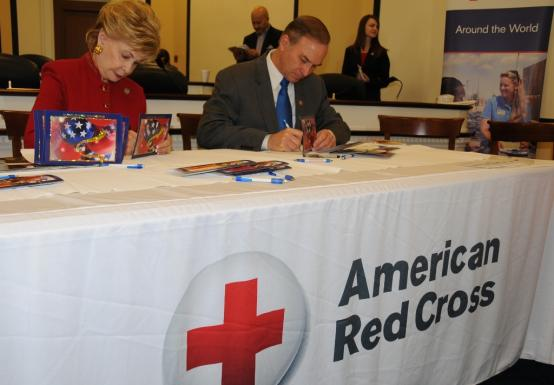 Congresswoman Bordallo signs holiday cards for servicemembers abroad.