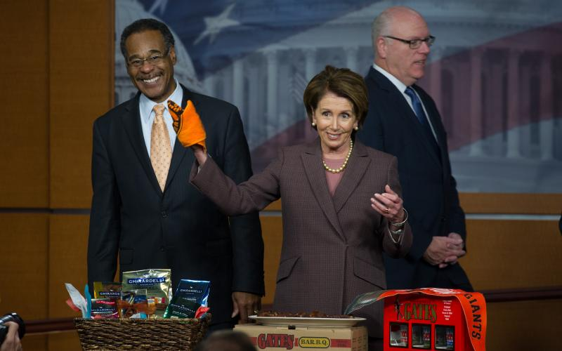 Congresswoman Pelosi and Congressman Emanuel Cleaver (D-MO) settle their friendly wager over the World Series between San Francisco Giants and the Kansas City Royals, with Gates Barbeque from Kansas City.