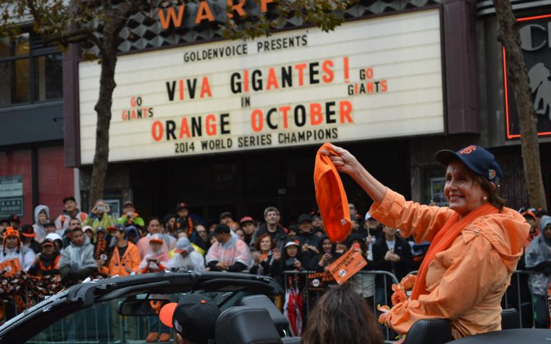 Congresswoman Pelosi waves to crowd during the San Francisco Giants' victory parade for their triumphant win as 2014 World Series Champions.